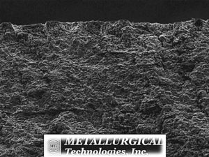 "Increased magnification SEM image of the opened ""A"" side crack surface along the ID reveals a corroded surface possibly obscuring the original crack morphology.(SEM Photo, Mag. 200X)"